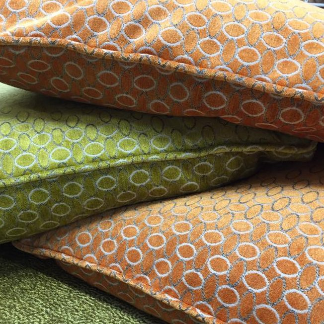 Orange and green pillow with circle patterns